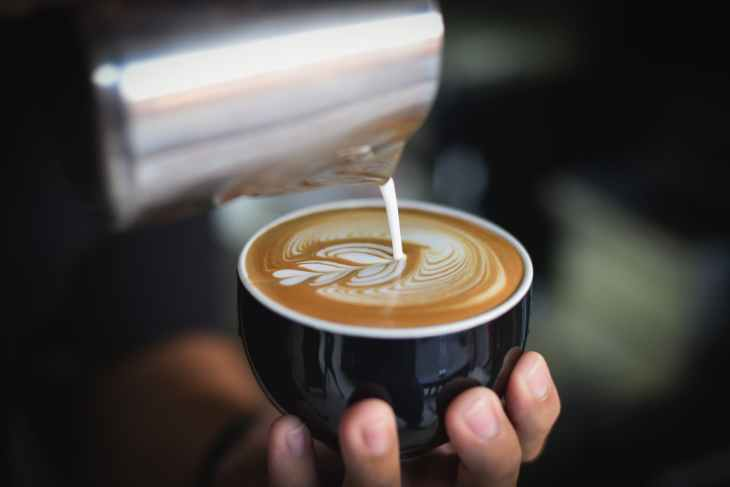 close up of woman holding coffee cup at cafe